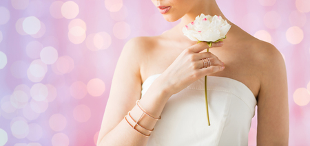 bride bangle: glamour, beauty, jewelry and luxury concept - close up of beautiful woman with golden ring and bracelet holding flower over pink holidays lights background Stock Photo