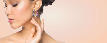 glamour luxury: glamour, beauty, jewelry and luxury concept - close up of beautiful woman face with earring over beige background Stock Photo