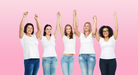 mid age: friendship, diverse, body positive and people concept - group of happy different size women in white t-shirts holding hands up over pink background
