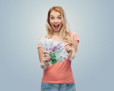お金、財政、投資、節約とコンセプト - 灰色の背景にユーロの現金お金と幸せの若い女性の人