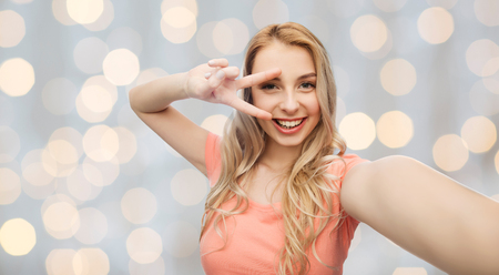 cute teen: emotions, expressions and people concept - happy smiling young woman taking selfie and showing peace hand sign over holidays lights background