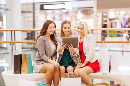 computer center: sale, consumerism, technology and people concept - happy young women with tablet pc and shopping bags in mall
