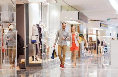 sprzedaż, konsumpcjonizm i koncepcja ludzie - szczęśliwa młoda para z torby na zakupy spaceru w centrum