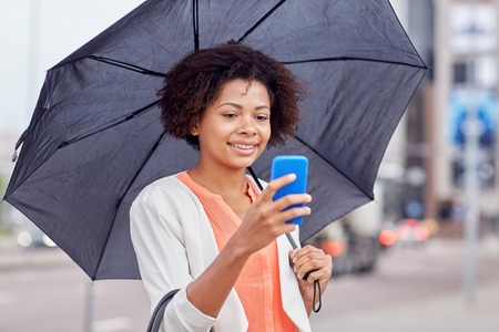 secure: business, bad weather and people and concept - happy african american businesswoman with umbrella texting on smartphone at city street Stock Photo