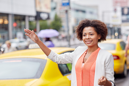 citylife: business trip, transportation and people concept - young smiling african american woman catching taxi at city street