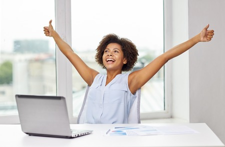 educación, los negocios, el éxito, el gesto y el concepto de tecnología - feliz africano americano de negocios o estudiante con ordenador portátil y documentos que muestran los pulgares hacia arriba y que celebran triunfo en la oficina