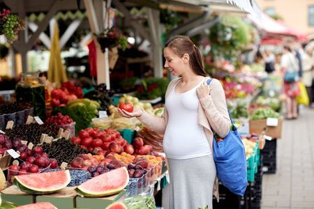 woman bag: sale, shopping, food, pregnancy and people concept - happy pregnant woman with bag holding tomato at street market