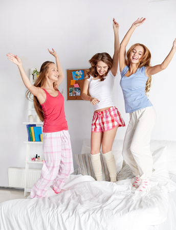 pj's: friendship, people and pajama party concept - happy friends or teenage girls having fun and jumping on bed at home Stock Photo