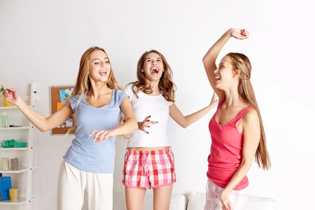 in pajama: friendship, people and pajama party concept - happy friends or teenage girls having fun and jumping on bed at home Stock Photo