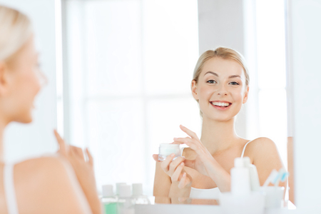 beauty skin: beauty, skin care and people concept - smiling young woman applying cream to face and looking to mirror at home bathroom