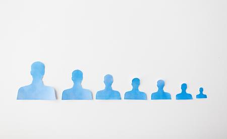 demografia: negocio, empleo, población, la carrera y la contratación concepto - cerca de la gente de papel da forma en la tarjeta blanca