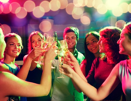 party, holidays, celebration, nightlife and people concept - smiling friends clinking glasses of champagne and beer in club Stock Photo