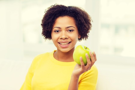 juicy: people, food, healthy eating and dental care concept - happy african american young woman with green apple at home Stock Photo