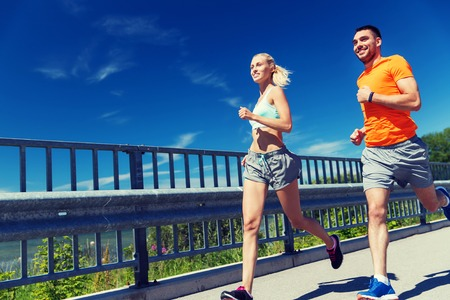 summer sport: fitness, sport, friendship and healthy lifestyle concept - smiling couple with heart-rate watch running at summer seaside Stock Photo