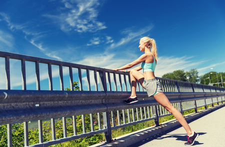 fense: fitness, sport, exercising and healthy lifestyle concept - smiling woman stretching leg outdoors