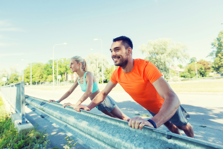 fitness, deporte, el entrenamiento y el concepto de estilo de vida saludable - cerca de la feliz pareja haciendo flexiones al aire libre