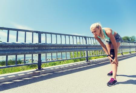 fitness, sport, lichaamsbeweging en gezonde levensstijl concept - jonge vrouw met knie brace gewond been buiten te ondersteunen