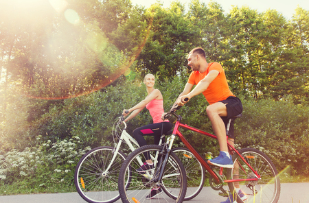 outdoor fitness: fitness, sport, people and healthy lifestyle concept - happy couple riding bicycle outdoors at summer