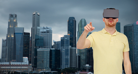 mediated: 3d technology, virtual reality, travel, entertainment and people concept - young man with virtual reality headset or 3d glasses playing game over singapore city skyscrapers background Stock Photo