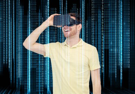 mediated: 3d technology, virtual reality, programming, entertainment and people concept - happy young man with virtual reality headset or 3d glasses over blue binary code numbers and black background Stock Photo