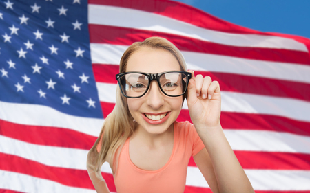 national, education and people concept - happy smiling young woman or teenage girl eyeglasses over american flag background Stock Photo