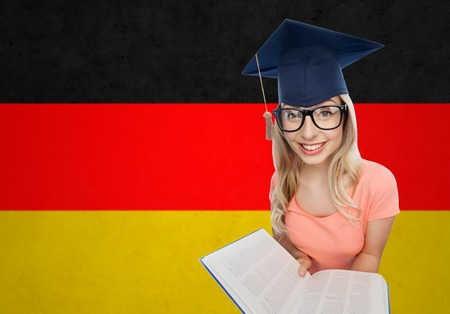 the encyclopedia: people, national education, knowledge and graduation concept - smiling young student woman in mortarboard and eyeglasses with encyclopedia book over german flag background Stock Photo