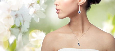 asian natural: beauty, jewelry, wedding accessories, people and luxury concept - close up of beautiful asian woman or bride with earring and pendant over natural spring cherry blossom background Stock Photo