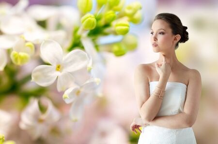 bride bangle: beauty, jewelry, wedding accessories, people and luxury concept - beautiful asian woman in white dress or bride with golden bracelet over natural spring lilac blossom background