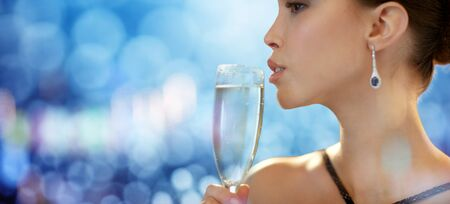 clubs diamonds: holidays, nightlife, drinks, people and luxury concept - close up of beautiful young asian woman drinking champagne at party over blue lights background