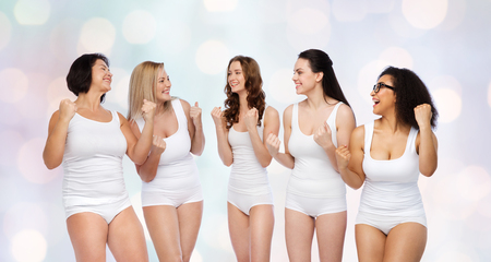 middle age women: success, friendship, beauty, body positive and people concept - group of happy different women in white underwear celebrating victory over holidays lights background Stock Photo