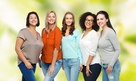 friendship, fashion, body positive, diverse and people concept - group of happy different size women in casual clothes over green natural background