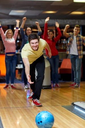 entertainment concept: people, leisure, sport and entertainment concept - happy young man throwing ball in bowling club