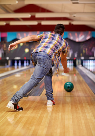 alley: people, leisure, sport and entertainment concept - happy young man throwing ball in bowling club