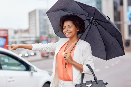 catching taxi: business trip, transportation and people concept - young smiling african american woman with umbrella catching taxi at city street
