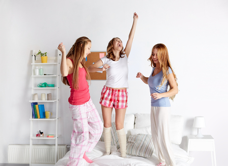 pajama party: friendship, people and pajama party concept - happy friends or teenage girls having fun and jumping on bed at home Stock Photo
