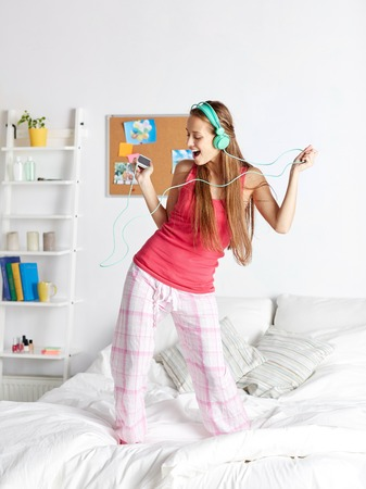 nightwear: people, leisure and technology concept - happy woman or teenage girl in headphones listening to music from smartphone and dancing on bed at home