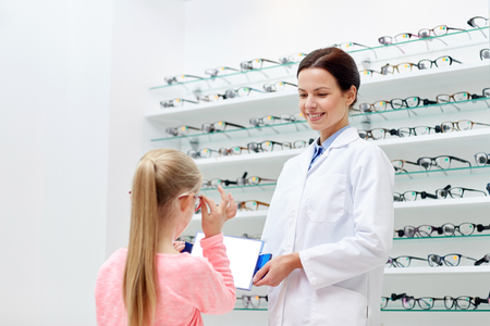 health care, people, eyesight and vision concept - optician with mirror helping little girl to choose glasses at optics store