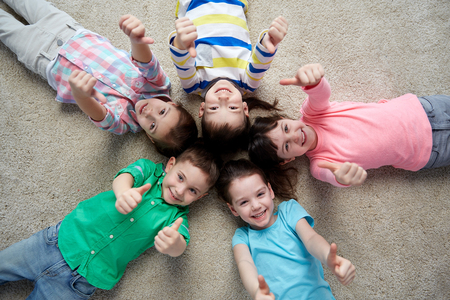 childhood, fashion, friendship and people concept - group of happy smiling little children lying on floor and showing thumbs up Foto de archivo