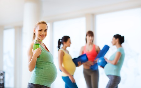 pregnant woman yoga: pregnancy, sport, fitness, people and healthy lifestyle concept - happy pregnant woman with water bottle in gym