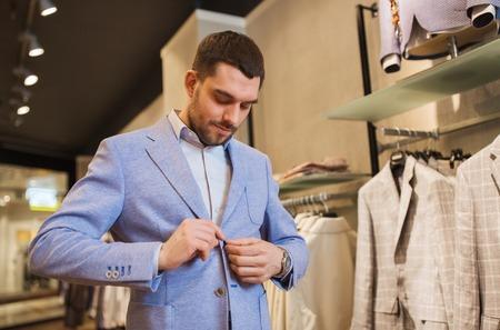 traje: venta, compras, moda, estilo y concepto de la gente - hombre joven elegante y tratando de elegir la chaqueta en el centro comercial o en una tienda de ropa Foto de archivo