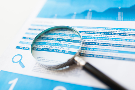 finance report: business, statistics, economy, finance and research concept - close up of financial report document and magnifying glass