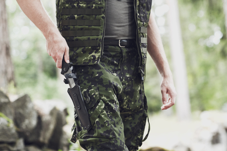 cold steel: war, army, cold steel arms and people concept - close up of young soldier, ranger or hunter hands taking out knife in forest