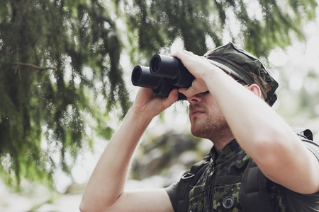 observing: hunting, war, army and people concept - young soldier, ranger or hunter with binocular observing forest