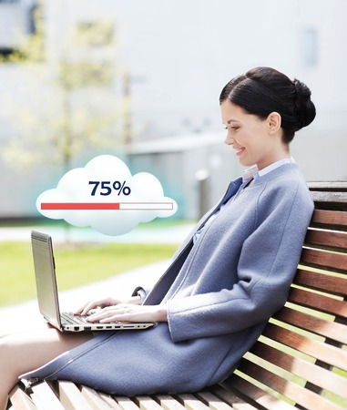 business, technology, cloud computing and people concept - young smiling woman with laptop computer and internet icon transferring data and sitting on bench in city