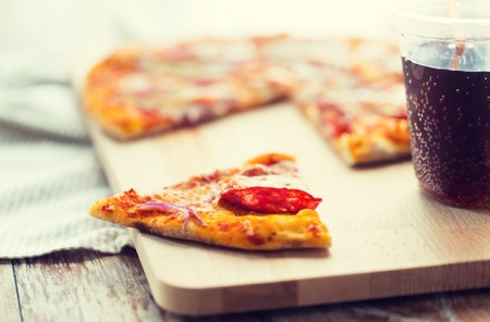 carbonated drink: fast food, italian kitchen and eating concept - close up of pizza slice and carbonated drink on wooden table