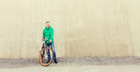 fixed: people, style, leisure and lifestyle - happy young hipster man with fixed gear bike on city street