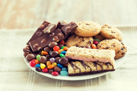 jellybean: junk food, sweets and unhealthy eating concept - close up of chocolate, oatmeal cookies, candies and muesli bars on plate