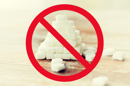 food, junk-food, diet and unhealthy eating concept - close up of white sugar pyramid on wooden table over red circle-backslash no sign Stock Photo