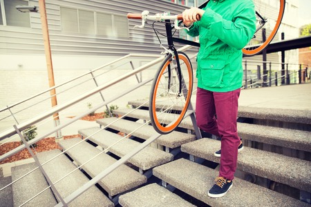 fixed: people, style, leisure and lifestyle - close up of man with fixed gear bike going downstairs Stock Photo