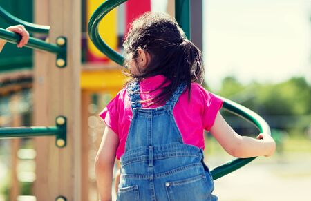 summer, childhood, leisure and people concept - close up of little girl playing on climbing frame at children playground